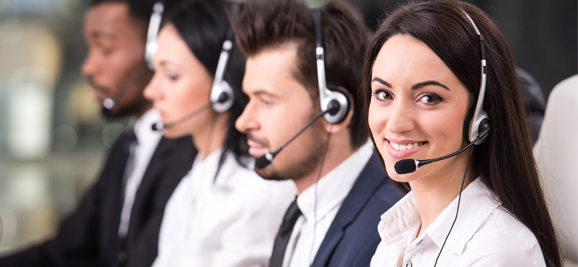 smiling female customer service agent with call center coworkers